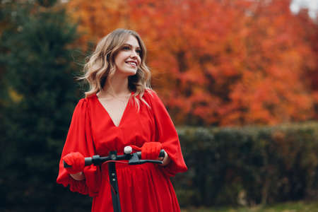 Young woman staying with electric scooter in red dress and smile at the autumn city park Stok Fotoğraf