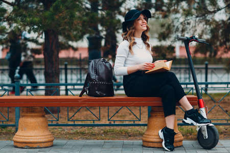 Young woman reading book and sitting on bench with electric scooter at the city Stok Fotoğraf