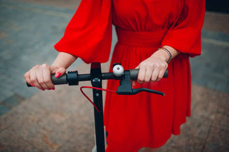 Young woman holds steering wheel of electric scooter in red dress at the city