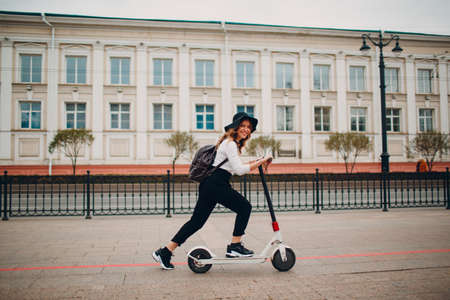 Young woman with electric scooter at the city Stok Fotoğraf
