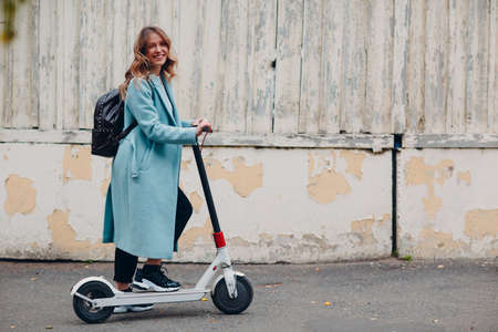 Young woman with e-scooter in blue coat at the city