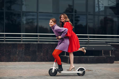 Two young women riding on electric scooter at the city