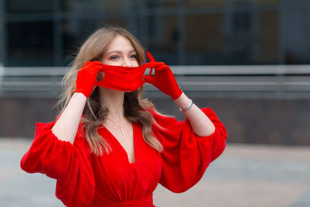 Young woman in red dress and gloves puts on medical protective face mask