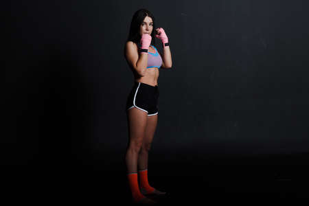 Sportsman muay thai woman boxer posing in training studio at black background.