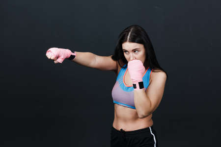 Sportsman woman boxer posing in training studio at black background.