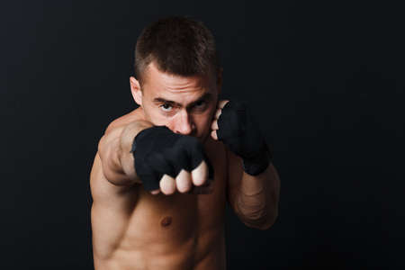 Sportsman man boxer stance punch jab at black background