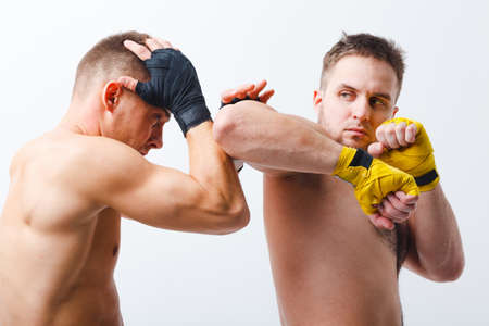 Two men boxers fighting muay thai boxing elbow white background