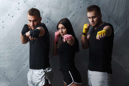 Three boxers man and woman posing before fighting muay thai boxing