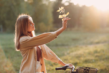 Happy active young woman holds fall leaves in hand and ride bicycle in autumn park Stok Fotoğraf