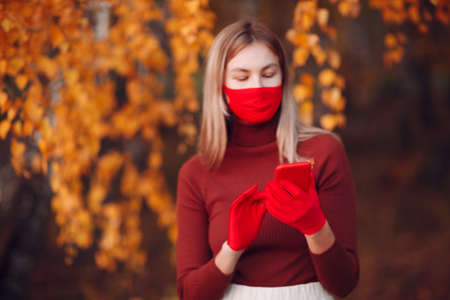 Active young woman in red gloves and face mask at autumn park with mobile phone Stok Fotoğraf