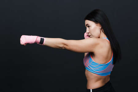 Sportsman muay thai strong woman boxer posing in training studio at black background.