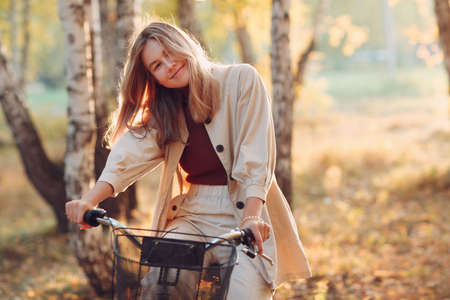 Happy smiling young woman riding vintage bicycle in autumn park at sunset Stok Fotoğraf