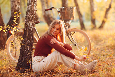 young woman sitting with vintage bicycle in autumn park Stok Fotoğraf