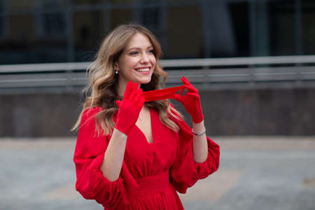 Young woman in red dress and gloves puts on medical face mask