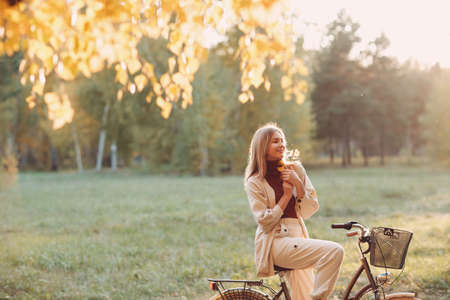 Happy active young woman holds fall leaves in hand ride bicycle in autumn park