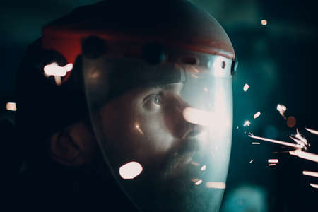 Man in transparent protective mask with flying sparks in darkness. Stok Fotoğraf