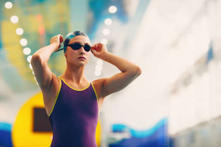 Young woman swimmer professional sportsman wearing cap and glasses at the swimming pool before the competition Stok Fotoğraf