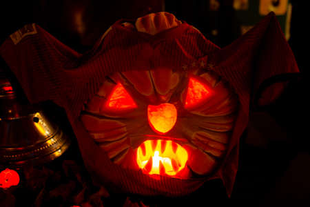 Halloween pumpkin head lantern with scary jack face in dark