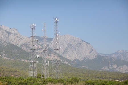 Telecommunication antenna tansmitter tower at mountains background. Stok Fotoğraf