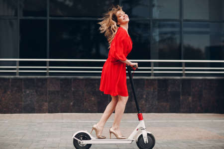 Young woman riding electric scooter in red dress and high-heeled shoes