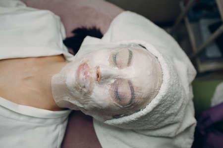 Paraffin Face Mask gauze bandage Therapy Young Woman Receiving Facial Skin Care Treatment. Beautician Pouring Wax Applying