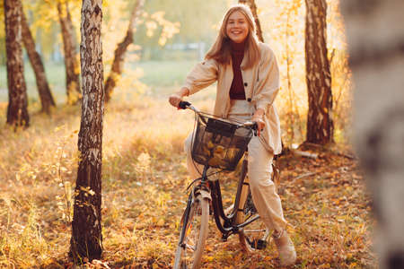 Happy active young woman riding vintage bicycle in autumn park at sunset