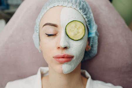 Young woman applying mask of clay on face with cucumber on eyes in beauty spa Standard-Bild
