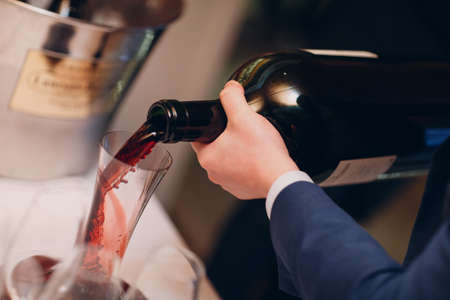 the waiter pours elite red wine into the decanter on the table in the restaurant