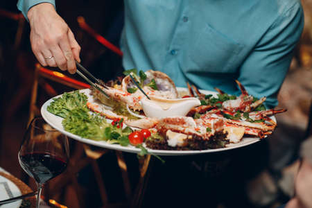 Waiter in a restaurant holds seafood dishes and serves a table catering Concept Healthy food octopus and crabs shellfish