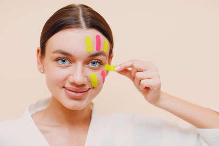 Beautiful caucasian woman applying tape lifting treatment on face