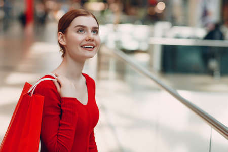 Young Woman with paper red bags in shopping mall. Black friday and shopping concept Standard-Bild