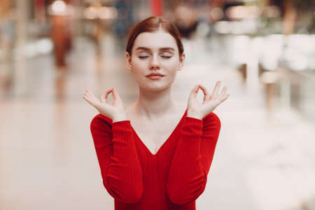 Portrait of young woman in shopping mall. Yoga, calm, zen and meditation concept