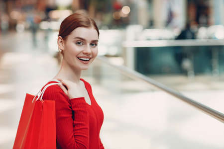 Young Woman with paper red bags in shopping mall. Black friday and Valentines day concept Standard-Bild