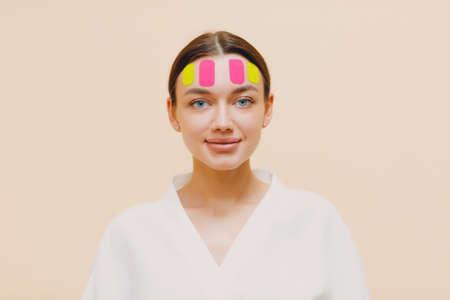 Beautiful woman applying tape lifting treatment on face