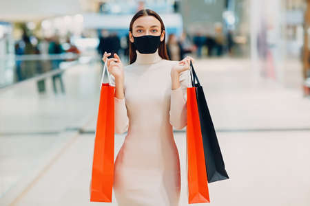 Positive young adult woman in face mask carrying paper shopping bags in hands