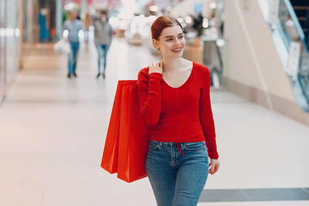 Young Smiling Woman walking with paper red bags in shopping mall.