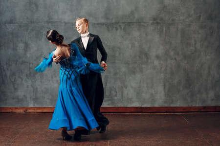 Ballroom foxtrot dancing. Young couple ballroom dancers. Studio shot