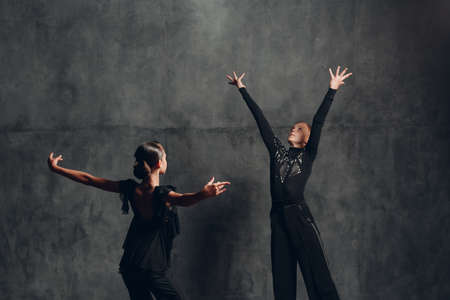 Couple dancers in black dress dancing in ballroom dances rumba.