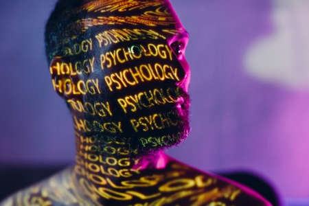 Young adult man with words Psychology on his face in the dark. Standard-Bild