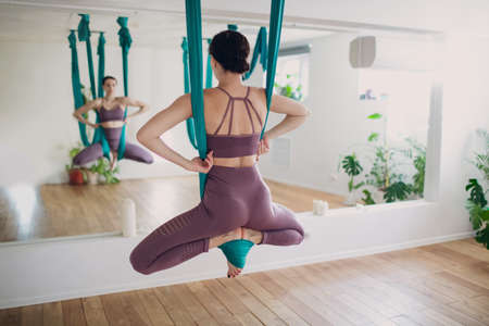 Aerial yoga concept. Woman practicing fly yoga in anti-gravity yoga studio using green hammock. Standard-Bild