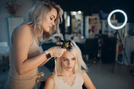 Hairdresser female making hair extensions to young woman with blonde hair in beauty salon. Professional hair extension. Standard-Bild