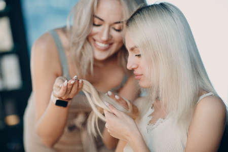 Hairdresser female making hair extensions to young woman with blonde hair in beauty salon. Professional strand hair extension. Standard-Bild