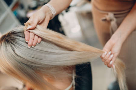 Hairdresser female making hair extensions to young woman with blonde hair in beauty salon. Professional hair extension strand of hair.