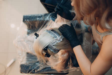 Young woman hairdresser dying hair at beauty salon. Professional hair roots coloring
