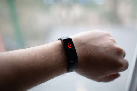 Male hand with fitness tracker with low charge battery symbol
