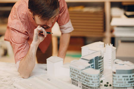 Architect Thoughtful with blueprints and layout design project at office Standard-Bild