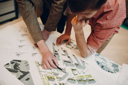 Architect with blueprints and layout design project at office