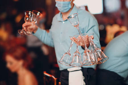 the waiter in the restaurant serves the tables and holds many transparent glasses in his hand catering concept Standard-Bild