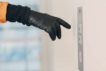 Close up of hand in glove forefinger pressing the button elevator during pandemic  quarantine concept