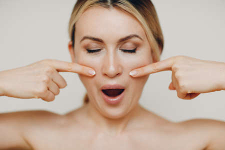 Young adult woman doing facial gymnastics self massage and rejuvenating exercises face building for skin and muscles lifting Standard-Bild